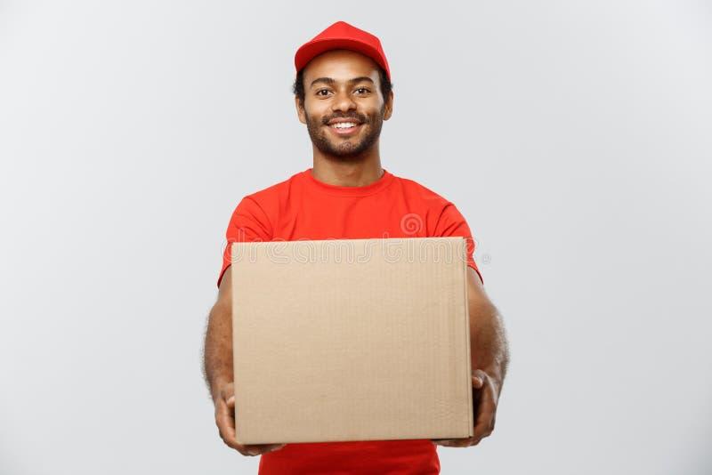 Concetto di consegna - ritratto del fattorino afroamericano felice in panno rosso che tiene un pacchetto della scatola Isolato su fotografia stock libera da diritti
