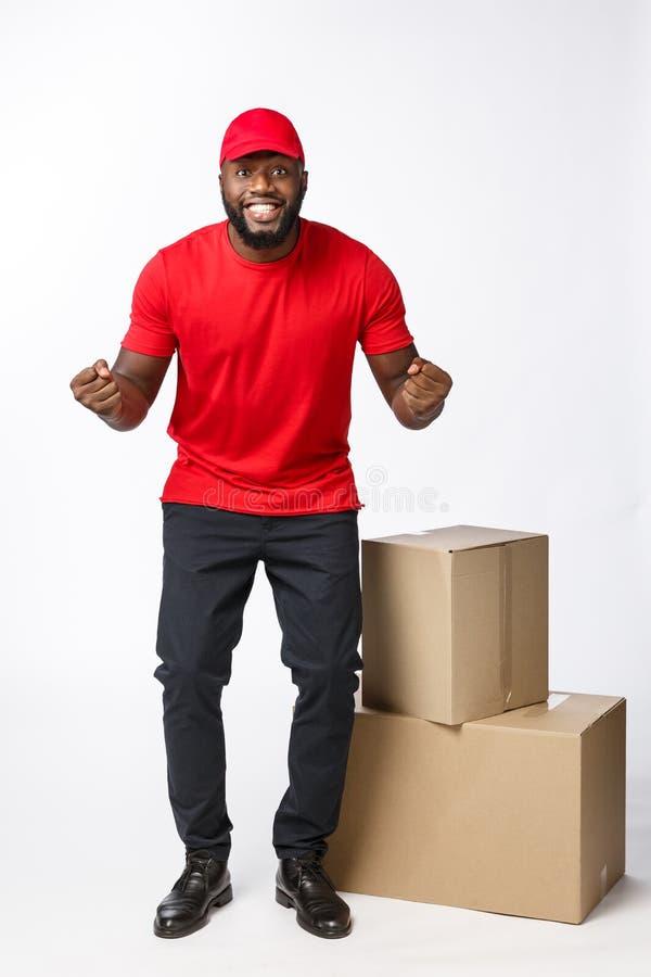 Concetto di consegna - ritratto del fattorino afroamericano felice in panno rosso che tiene un pacchetto della scatola Isolato su fotografie stock