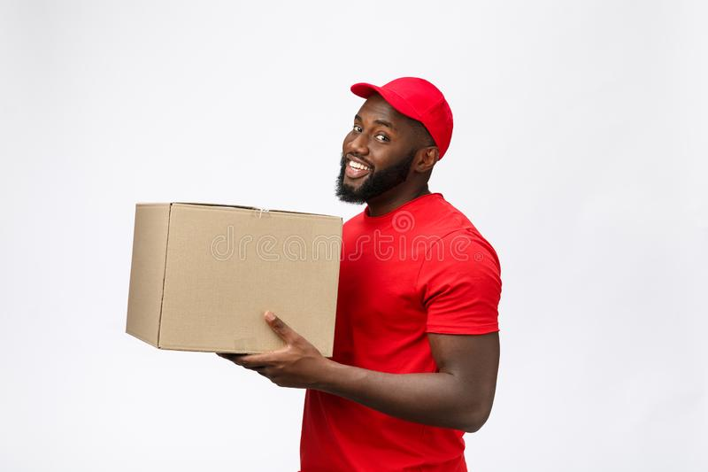 Concetto di consegna - ritratto di vista laterale del fattorino afroamericano felice in panno rosso che tiene un pacchetto della  immagini stock