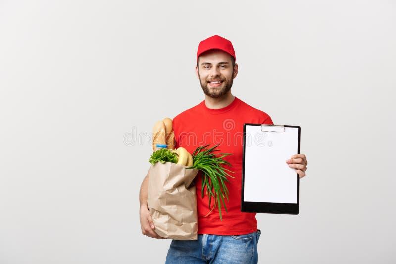 Concetto di consegna: Uomo caucasico bello del corriere di consegna della drogheria in uniforme di rosso con il contenitore di dr immagini stock libere da diritti