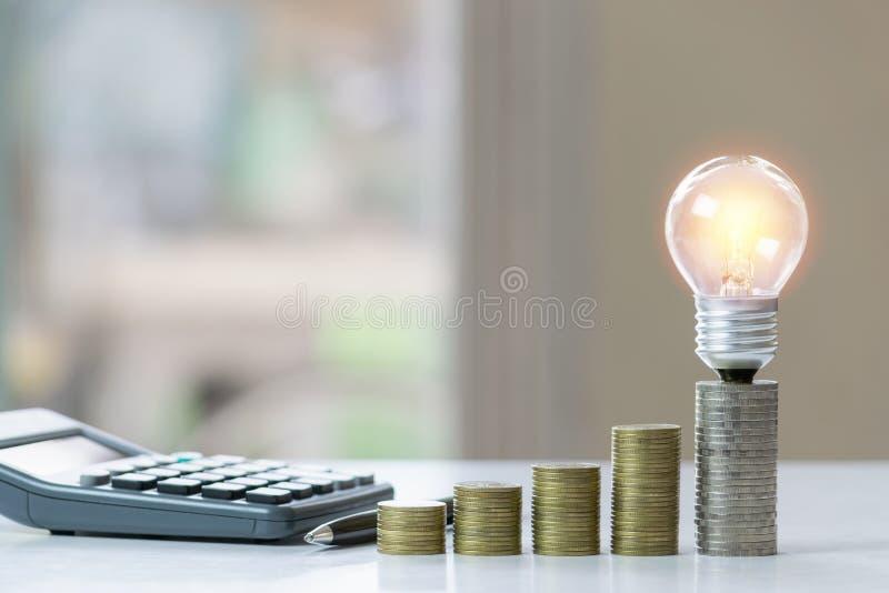 Concetto di contabilit? con le monete, la lampadina ed il calcolatore sulla tavola fotografia stock