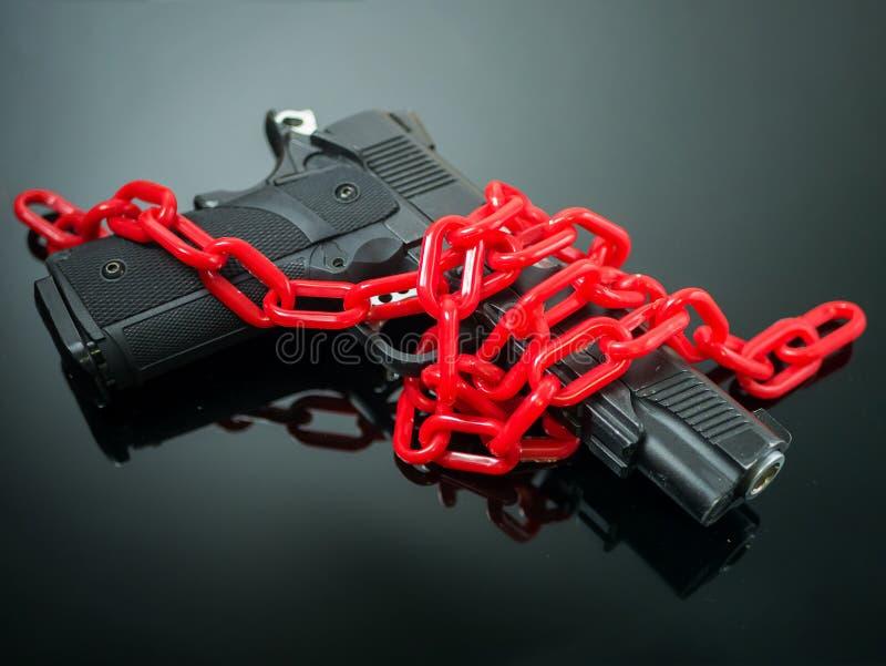 Concetto di controllo delle armi di riforma catena di rosso intorno alla rivoltella sul nero fotografia stock