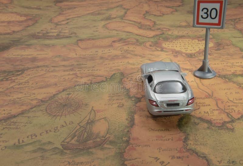 concetto di corsa Automobile del giocattolo sulla mappa di mondo d'annata con il segnale stradale immagini stock libere da diritti