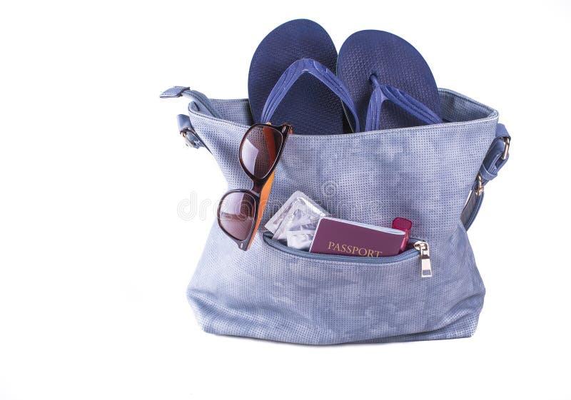 concetto di corsa Borsa della donna con le pantofole della spiaggia, occhiali da sole, passaporto, preservativi, rossetto immagini stock libere da diritti