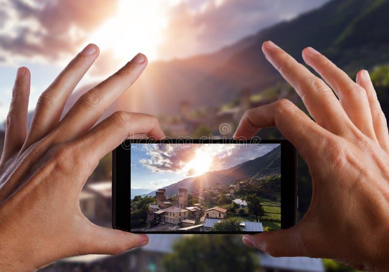 concetto di corsa Mani che fanno foto di vecchio villaggio di Svaneti in Georgia Torre medievale Mestia fotografia stock libera da diritti