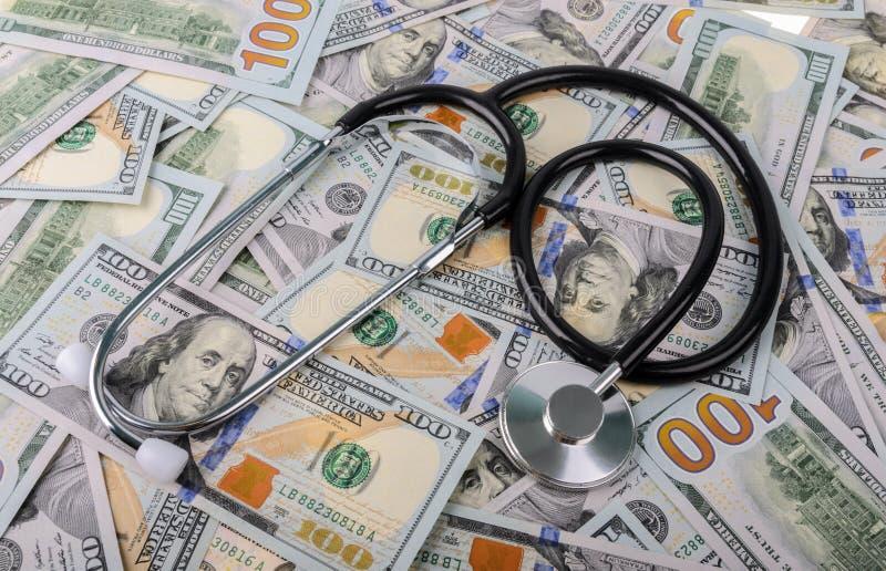 Concetto di costo e di trattamento medico: stetoscopio che dispone sulle banconote dei dollari americani immagine stock