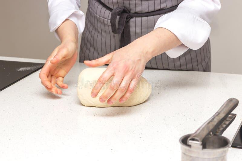 Concetto di cottura Le donne lavorarici dure prepara la pasticceria solo, impasta la pasta sul contatore di legno con farina ed i fotografia stock