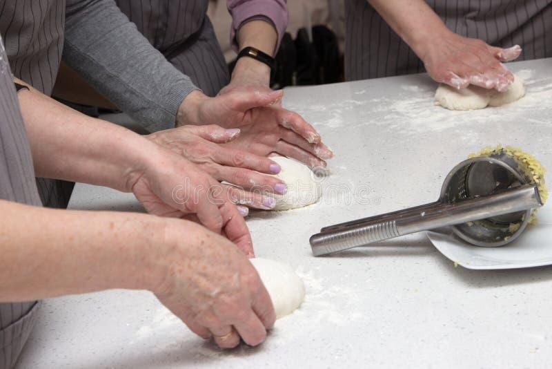 Concetto di cottura Le donne lavorarici dure prepara la pasticceria solo, impasta la pasta sul contatore di legno con farina ed i fotografia stock libera da diritti