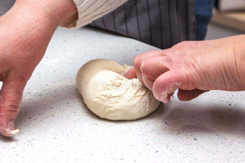 Concetto di cottura Le donne lavorarici dure prepara la pasticceria solo, impasta la pasta sul contatore di legno con farina ed i fotografie stock