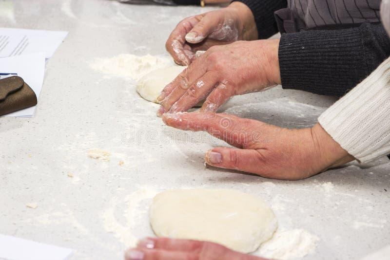 Concetto di cottura Le donne lavorarici dure prepara la pasticceria solo, impasta la pasta sul contatore di legno con farina ed i immagini stock