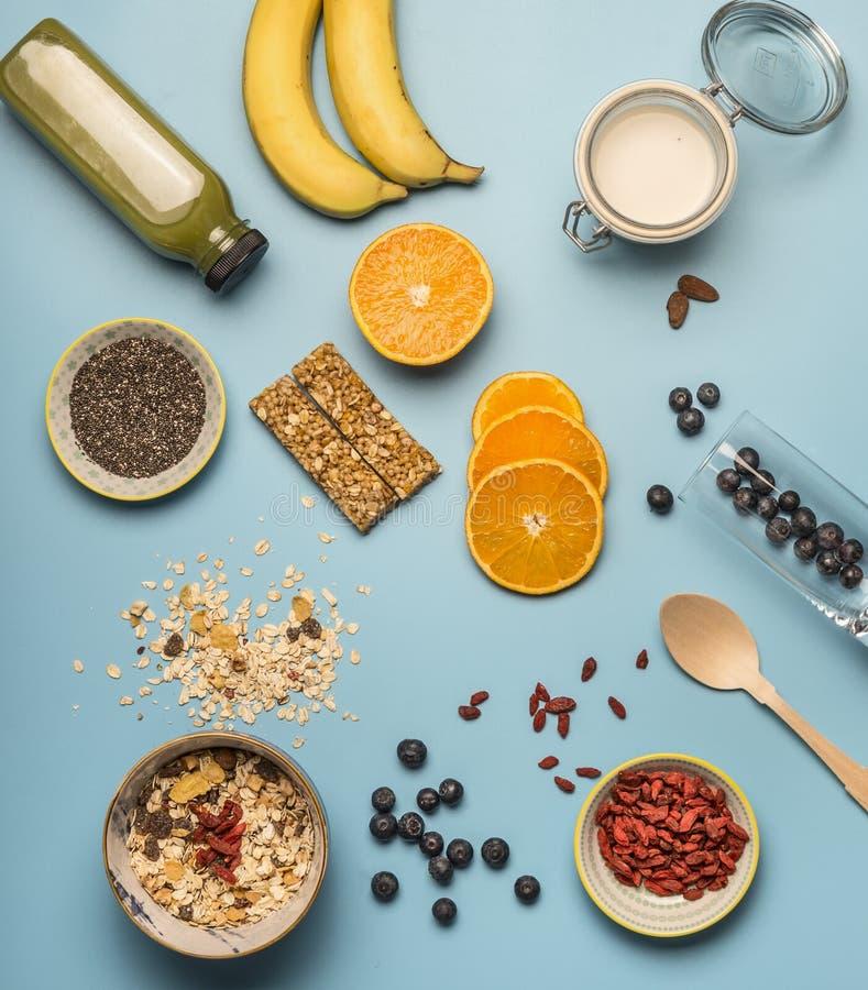Concetto di cottura prima colazione sana, le bacche, le banane, i frullati, i mirtilli, le arance, i cereali, le barre nutrienti  immagine stock