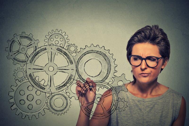 Concetto di creatività di idee e degli ingranaggi Donna in vetri che estraggono gli ingranaggi con la penna immagine stock