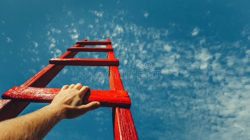 Concetto di crescita di carriera di motivazione di raggiungimento di sviluppo Equipaggia la mano che raggiunge per la scala rossa fotografie stock libere da diritti