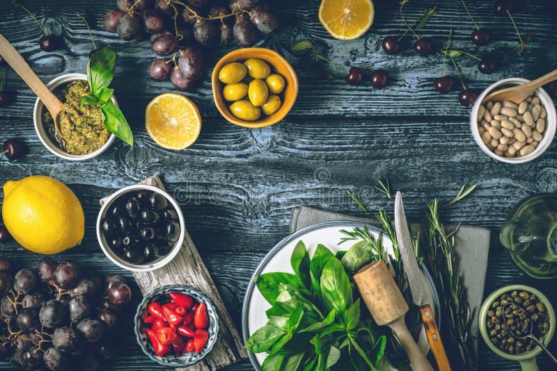 Concetto di cucina Mediterranea Frutta, erbe ed aperitivi differenti sull'orizzontale di legno della tavola immagine stock