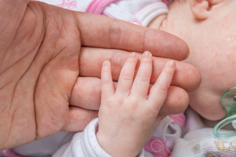 Concetto di cura del bambino Il bambino tiene la mano di suo padre immagini stock libere da diritti
