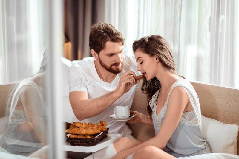 Concetto di cura e di amore Il giovane maschio barbuto bello affettuoso alimenta la sua amica sveglia con il croissant, si siede  immagine stock libera da diritti