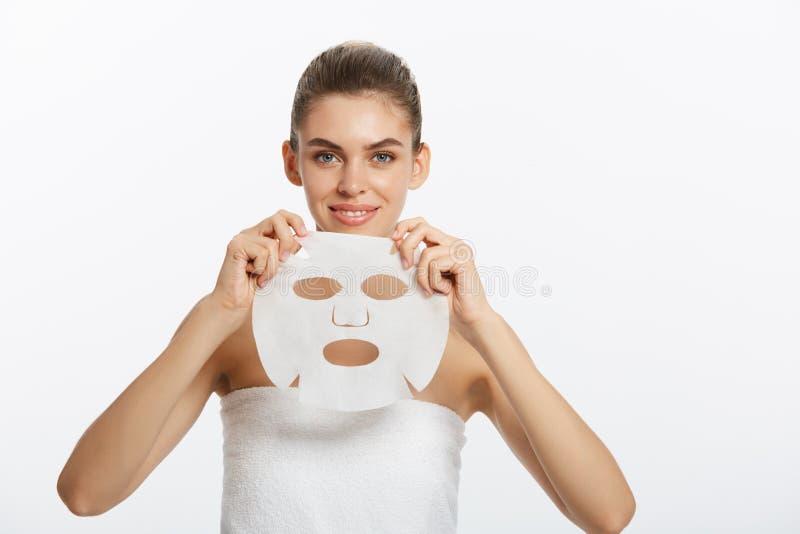 Concetto di cura di pelle di bellezza - bella donna caucasica che applica la maschera di carta dello strato sul suo fondo di bian fotografia stock