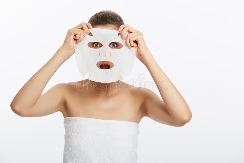 Concetto di cura di pelle di bellezza - bella donna caucasica che applica la maschera di carta dello strato sul suo fondo di bian fotografie stock libere da diritti