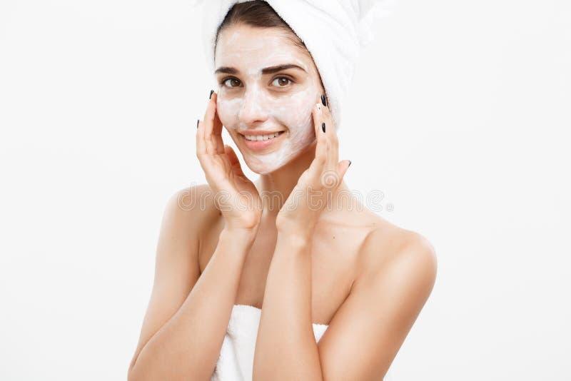 Concetto di cura di pelle di bellezza - bello ritratto caucasico del fronte della donna che applica maschera crema sul suo bianco fotografia stock