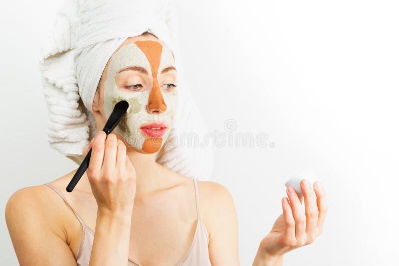 Concetto di cura di pelle di procedure di bellezza Giovane donna che applica la maschera grigia e rossa facciale dell'argilla del immagine stock libera da diritti