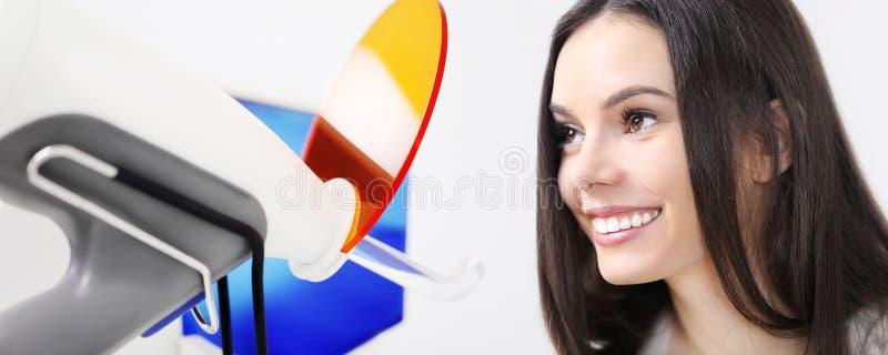 Concetto di cure odontoiatriche, bella donna sorridente con il briciolo del ` s del dentista immagine stock