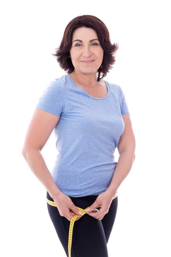 Concetto di dieta - bella donna matura sportiva esile con la misura t fotografia stock libera da diritti