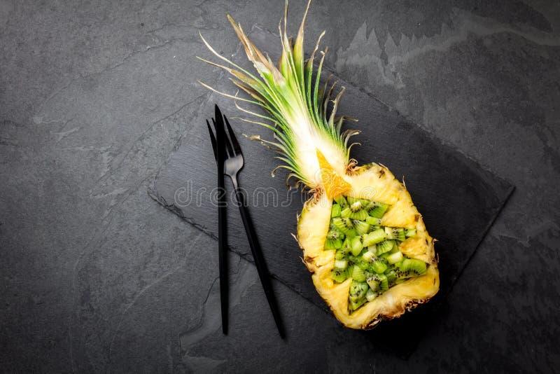 Concetto di dieta di festa o concetto tropicale del menu di Natale L'albero di Natale fatto dall'ananas ed il kiwi sull'ardesia i fotografie stock
