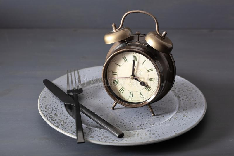 Concetto di digiuno intermittente, dieta ketogenic, perdita di peso forcella e coltello della sveglia su un piatto immagini stock libere da diritti