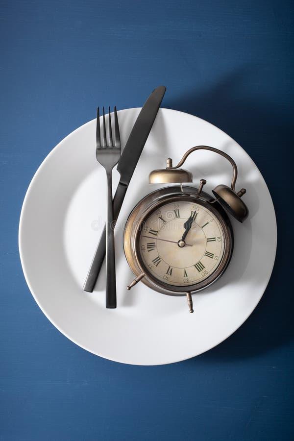 Concetto di digiuno intermittente, dieta ketogenic, perdita di peso forcella e coltello della sveglia su un piatto immagini stock