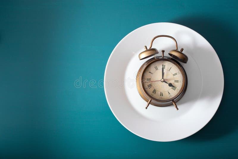 Concetto di digiuno intermittente, dieta ketogenic, perdita di peso sveglia su un piatto immagini stock