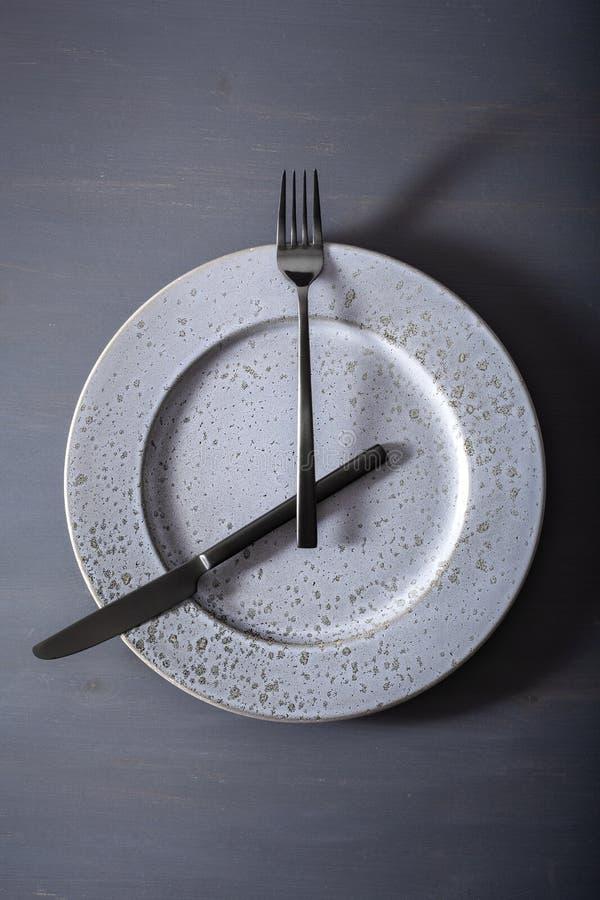 Concetto di digiuno intermittente e della dieta ketogenic, perdita di peso la forcella ed il coltello hanno attraversato su un pi fotografia stock libera da diritti