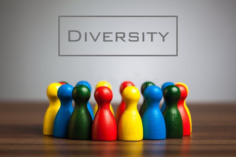 Concetto di diversità con le figurine del pegno sulla tavola fotografia stock