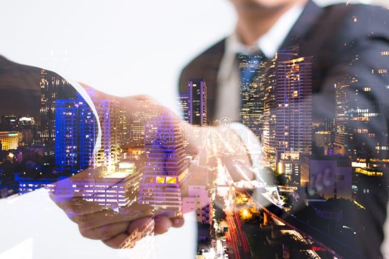 Concetto di doppia esposizione Stretta di mano di affari dell'investitore con la notte della città Uomo d'affari che agita le man immagini stock