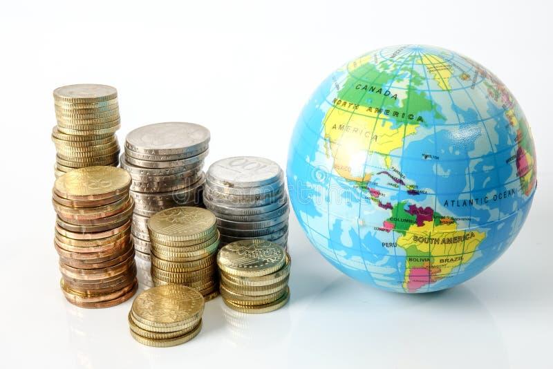 Concetto di economia globale con il globo della sfera ed impilato delle monete sopra bianco fotografie stock libere da diritti
