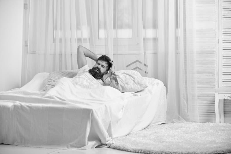 Concetto di emicrania Tipo sul fronte doloroso che sveglia nella mattina Equipaggi mettere sul letto, la testa commovente, tenda  fotografia stock