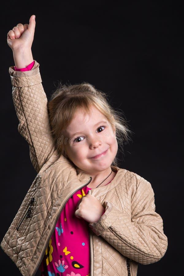 Concetto di emozione: bambina felice con un braccio alzato Fondo nero, foto dello studio immagine stock