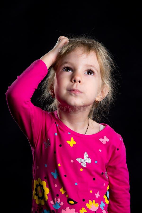Concetto di emozione: bambina interessata Fondo nero, foto dello studio fotografia stock libera da diritti