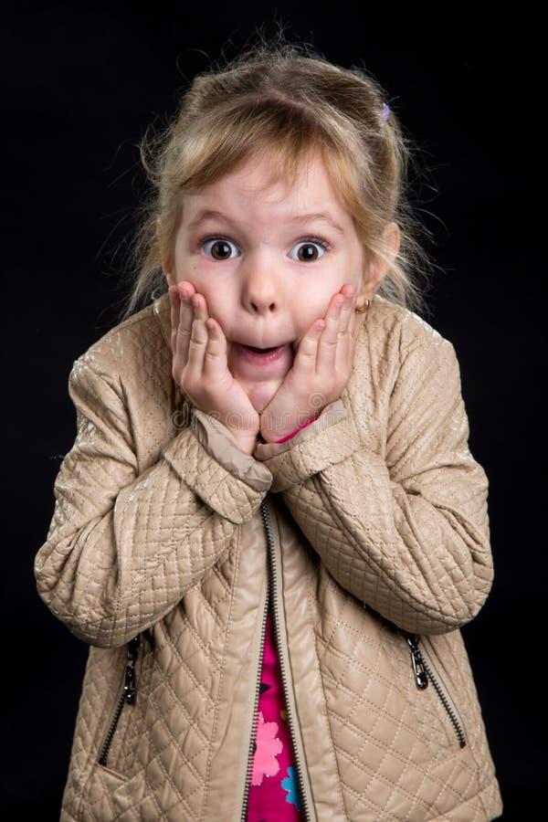 Concetto di emozione: bambina stupita Fondo nero, foto dello studio fotografia stock libera da diritti