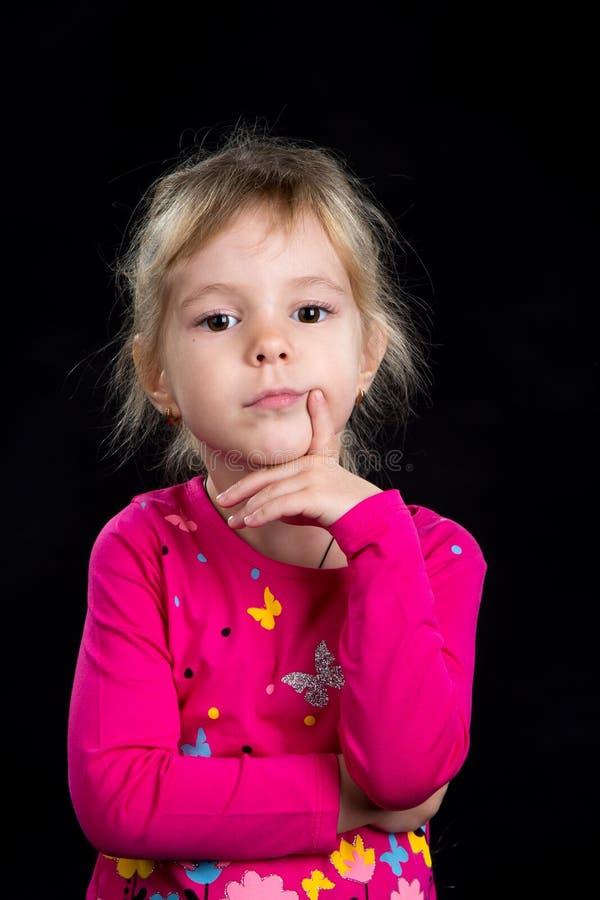 Concetto di emozione: bambina triste pensierosa Fondo nero, foto dello studio immagini stock libere da diritti