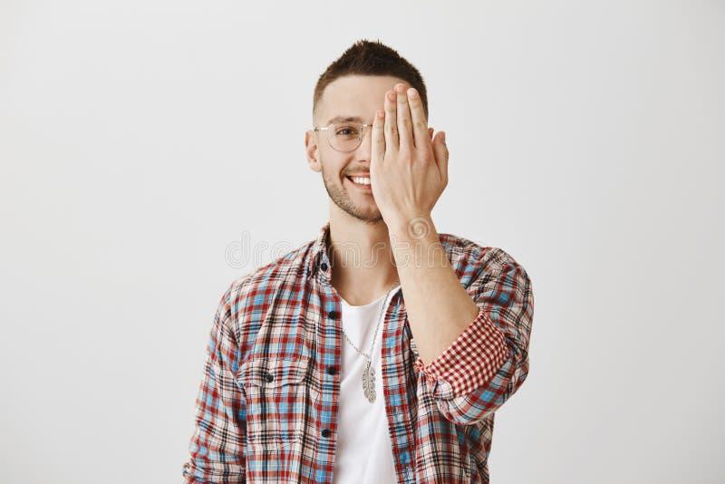 Concetto di emozioni della gente Ritratto dell'uomo attraente in vetri che nascondono metà del fronte con la palma mentre sorride immagini stock