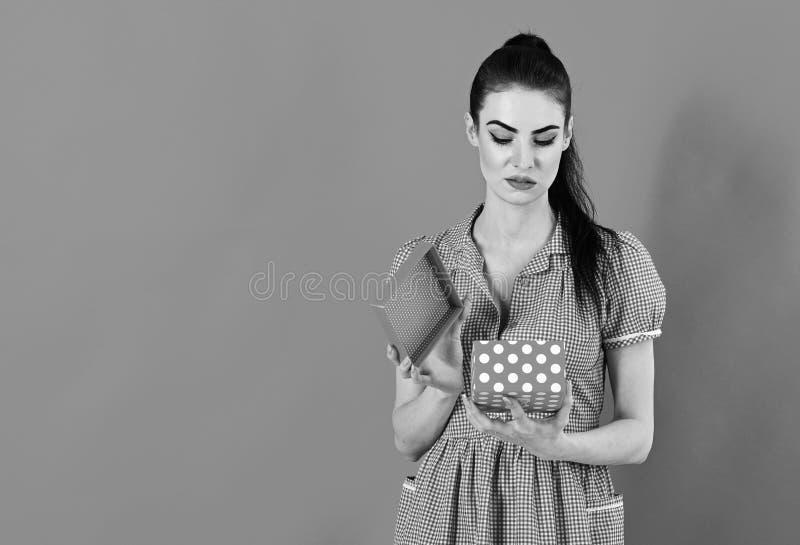 Concetto di emozioni e di delusione La donna apre il contenitore di regalo e ritiene la delusione immagine stock libera da diritti
