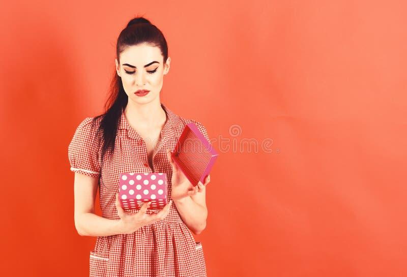 Concetto di emozioni e di delusione La donna apre il contenitore di regalo e ritiene la delusione immagine stock