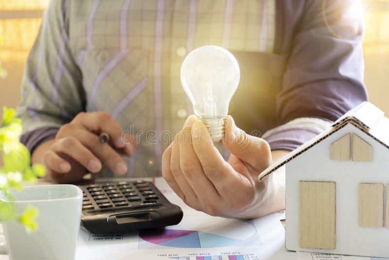 Concetto di energia Uomini che stanno calcolando le riduzioni dei costi da energia Mano che tengono una lampadina e una matita Mo fotografia stock