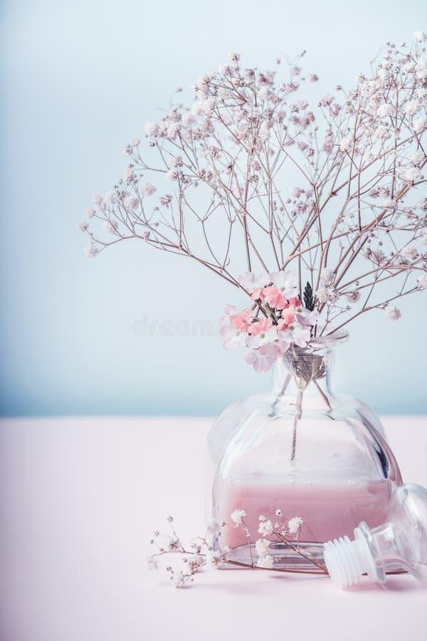 Concetto di erbe di benessere o del cosmetico Barattolo di vetro con lozione rosa e fiori a colore pastello fotografia stock