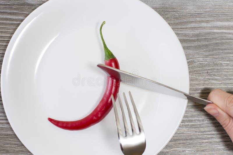 Concetto di essere a dieta rigoroso Chiuda sulla foto delle mani del ` s della donna che tagliano il peperoncino su un'ustione de immagine stock