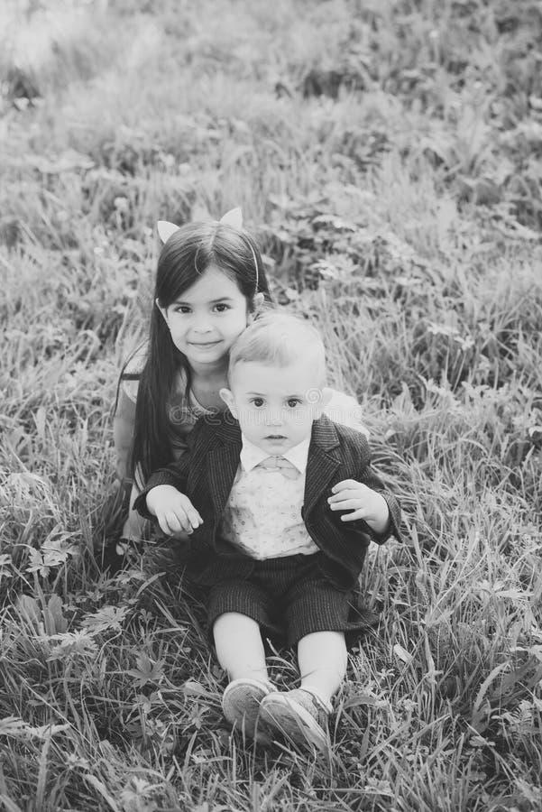 Concetto di felicità dei bambini di infanzia del bambino I bambini si siedono su erba verde, vacanze estive immagini stock