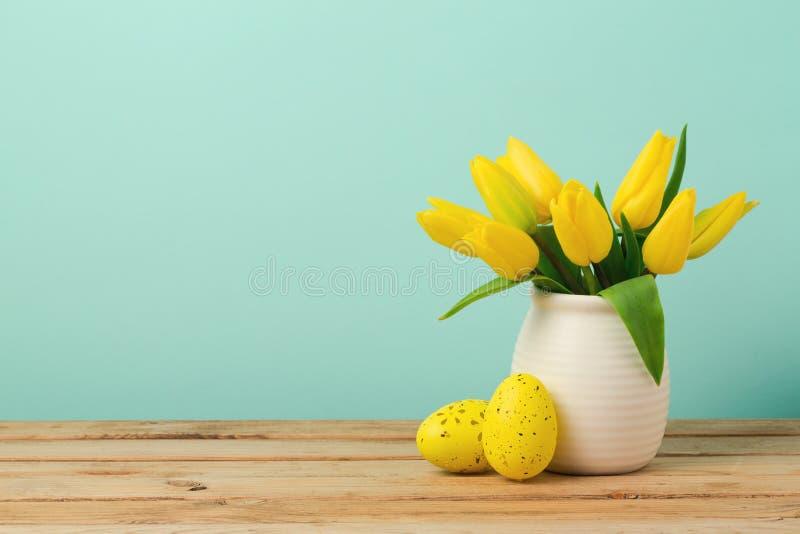 Concetto di festa di Pasqua con le decorazioni dei fiori e delle uova del tulipano sulla tavola di legno