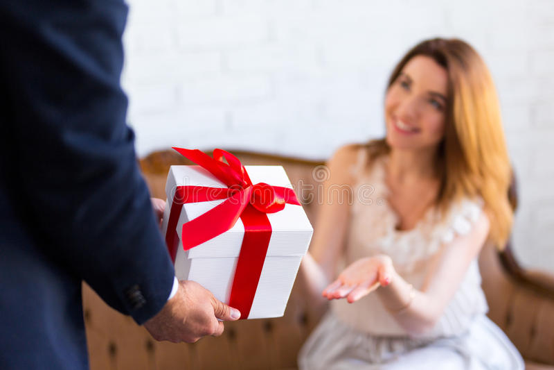 Concetto di festa - equipaggi dare il contenitore di regalo alla sua amica o moglie immagini stock