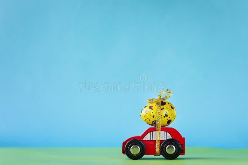 Concetto di festa di Pasqua - automobile rossa del giocattolo che porta uovo giallo Immagine tonificata immagini stock