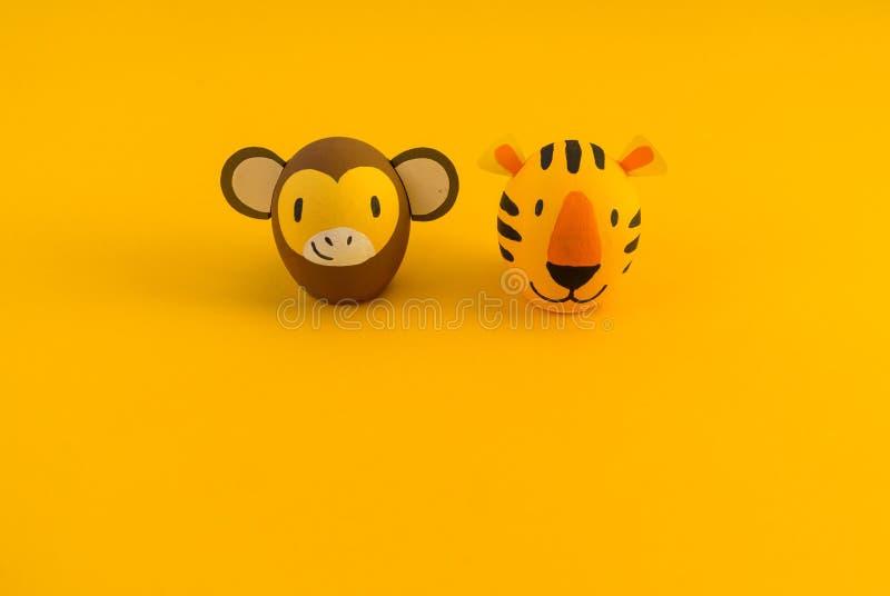 Concetto di festa di Pasqua con le uova fatte a mano sveglie: tigre e scimmia arancio fotografie stock